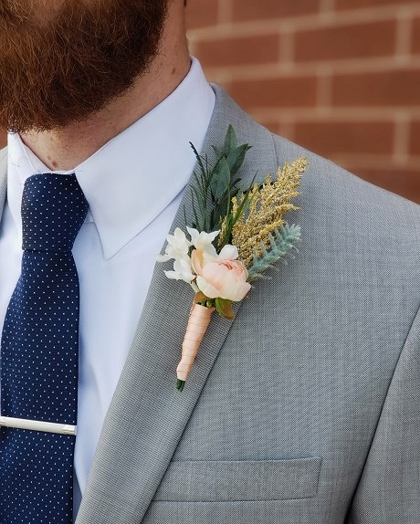 The Oslo boutonniere on a groomsman in a navy tie