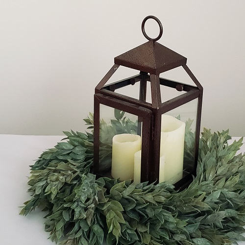A bronze lantern with three LED candles and a faux ruscus wreath