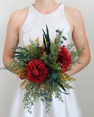 Artificial juniper and red ball dahlias in a rentable bouquet