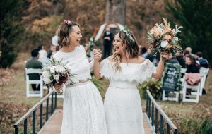Two brides walking down the aisle after getting married