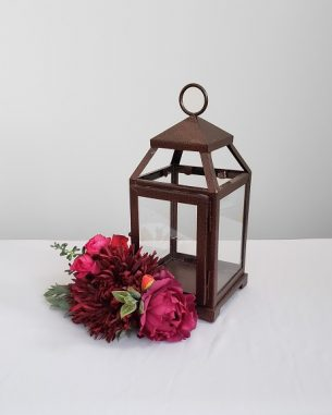 Decorative faux flowers paired with a bronze lantern