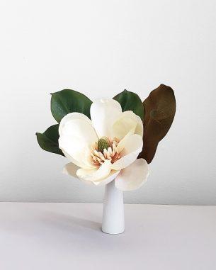 A single artificial magnolia bloom as a small centerpiece