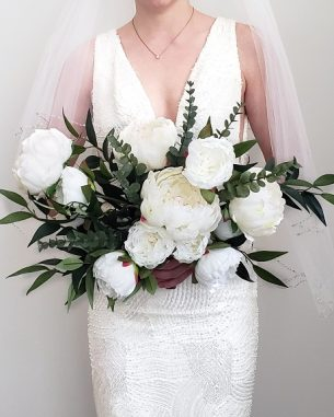 Artificial white peonies and faux smilax in a hand-tied bouquet of silk flowers.