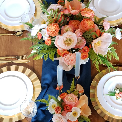 A tablesetting with bright orange centerpieces and a blue runner.