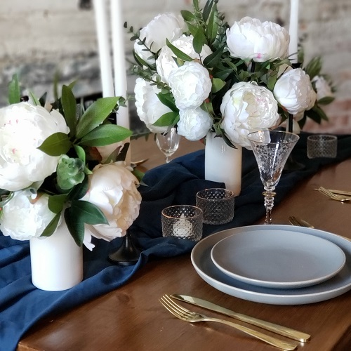 A tablesetting with a dark blue runner and white peony centerpieces.