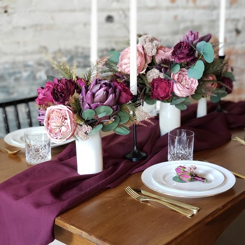 Purple centerpieces on a wood table laid with white place and a purple runner.