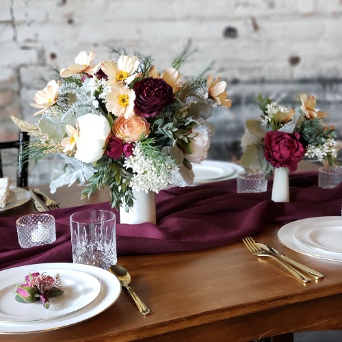 Wildflower centerpieces on a wood table laid with white place and a purple runner.