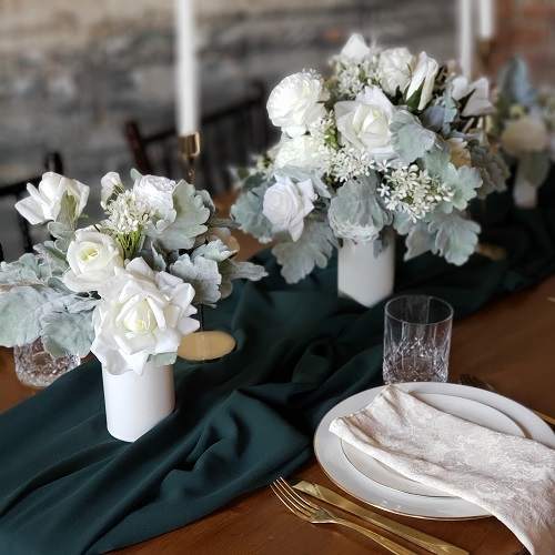 Dusty miller and white ranunculus centerpieces with a dark green runner and white taper candles.