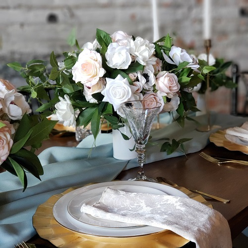 A tablesetting with white gardenia and pink rose centerpieces.