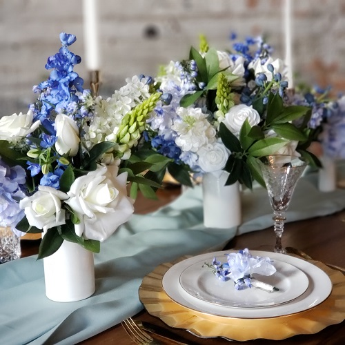 Blue delphinium centerpieces with gold and white tablesetting details.