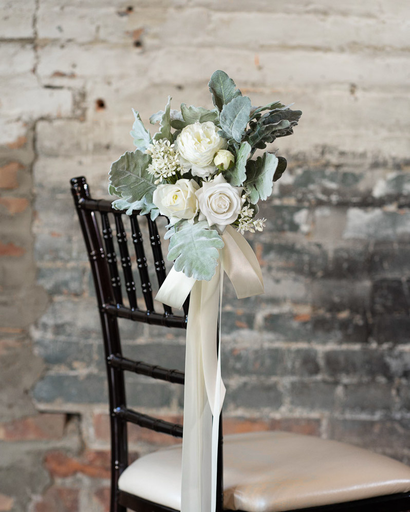 A white rose aisle marker tied with white ribbon on a Chiavari chair.