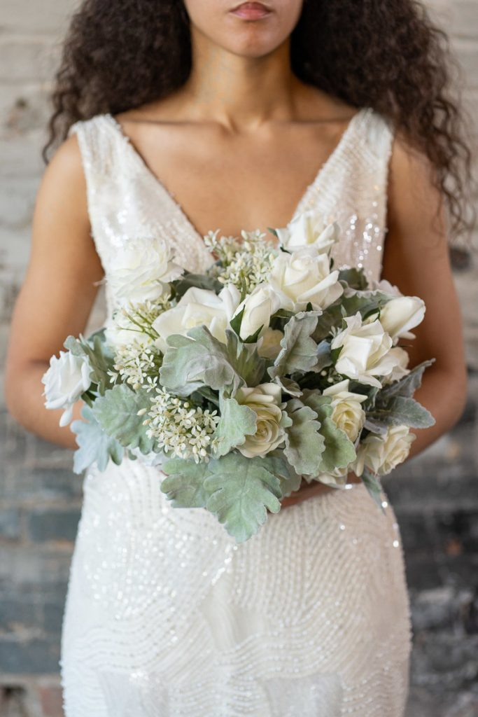 A bride with a white rose and dusty miller bridal bouquet from the Florence Collection.