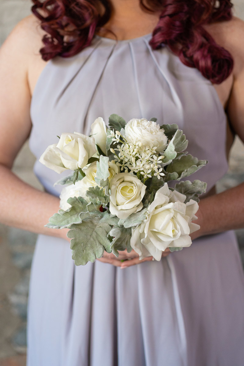 A bridesmaid in a grey dress with white rose bouquet from the Florence Collection.