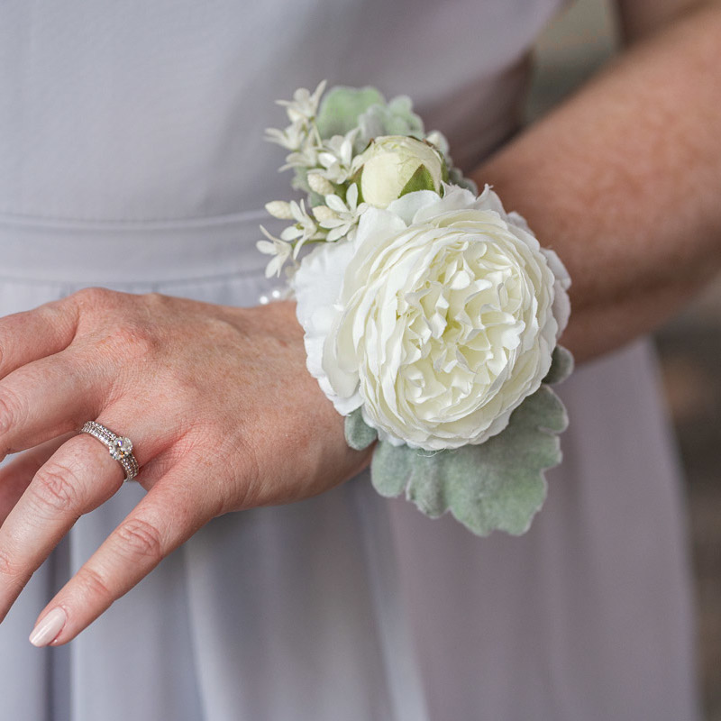 A bridesmaid with a white ranunculus corsage from the Florence Collection.
