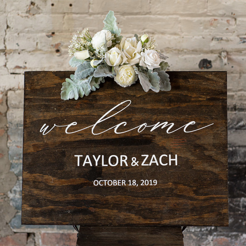 A wood sign with a white rose floral sign swag.