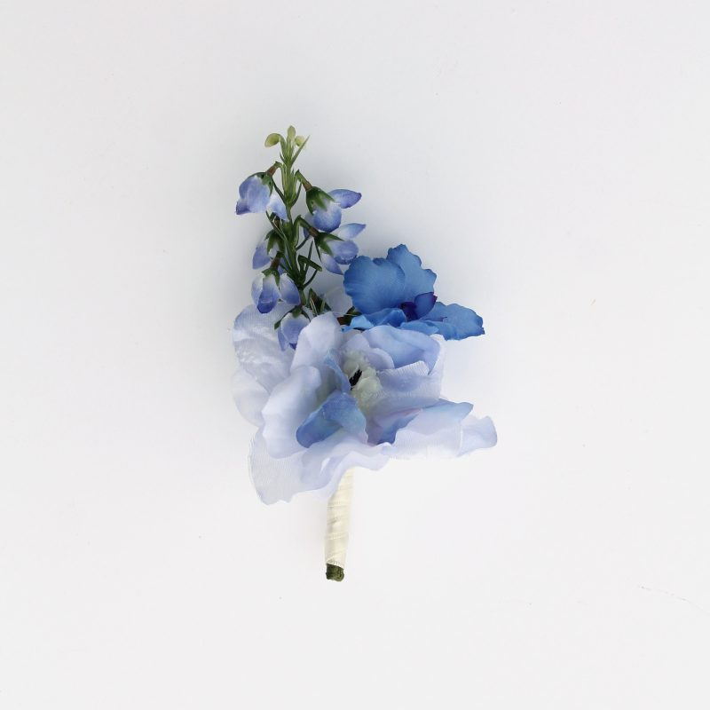A blue delphinium boutonniere from the Juneau Collection.