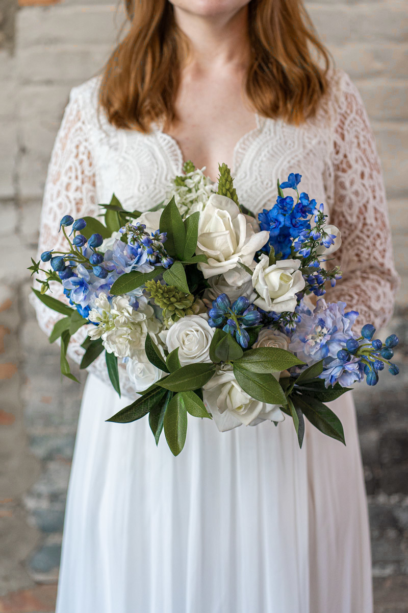 A bride with a large blue and white delphinium bridal bouquet from the Juneau Collection