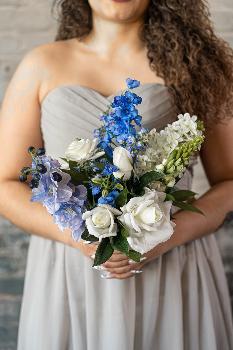 A bridesmaid in a grey dress with a blue bouquet from the Juneau Collection.