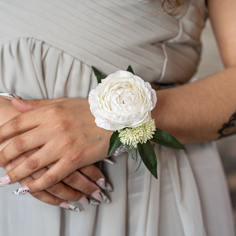 A white ranunculus corsage on a bridesmaid in a grey dress.