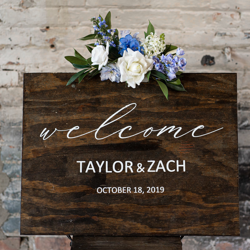 A wood sign with a blue floral sign swag from the Juneau Collection.