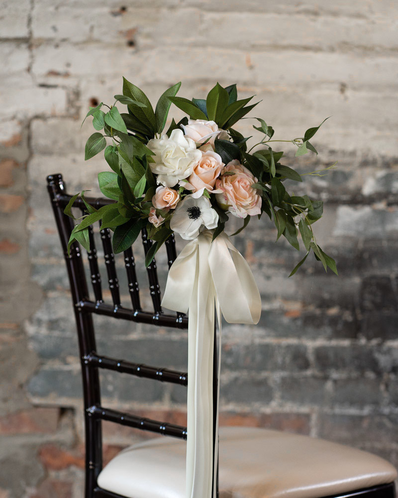 A floral aisle marker with white anemones, gardenias, and pink roses.