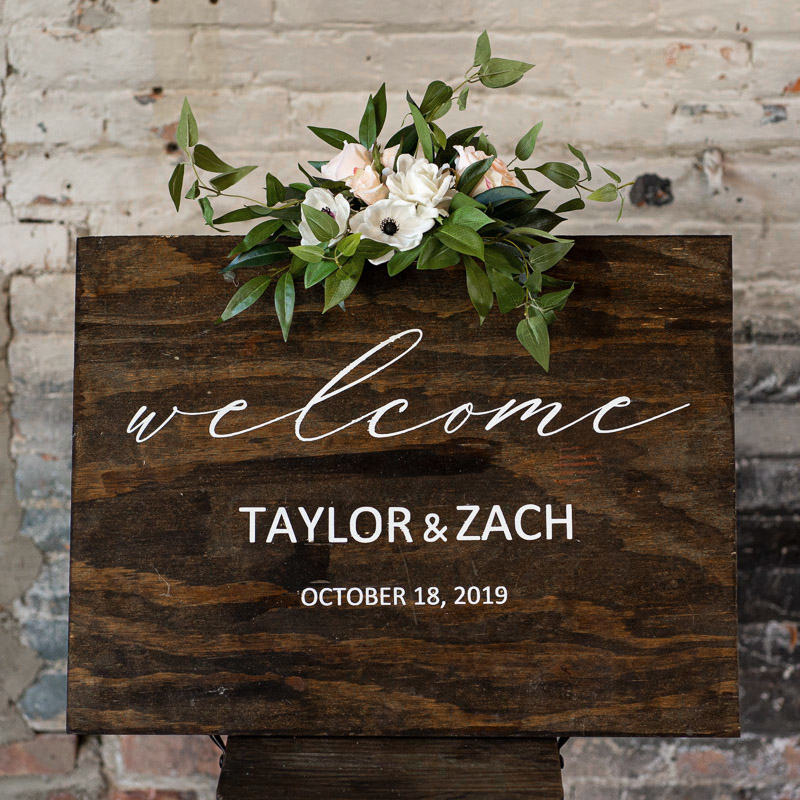 A wood sign with a gardenia and anemone sign swag.