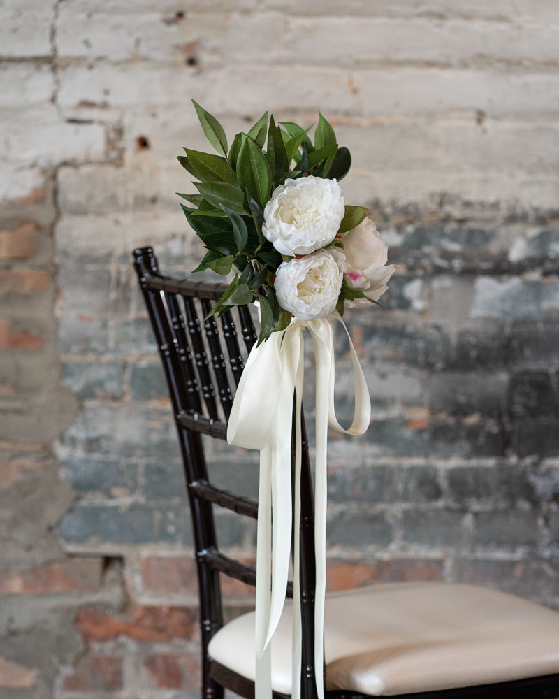 A white peony and dark greenery aisle marker tied to a Chiavari chair with white ribbon.
