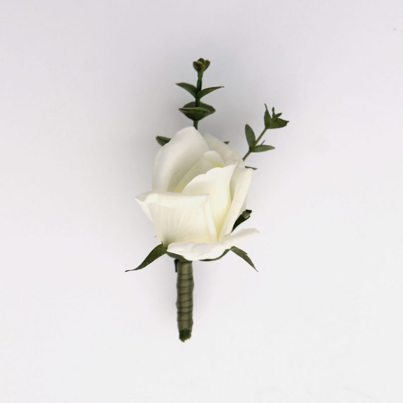 A white rose boutonniere from the Lhasa Collection.
