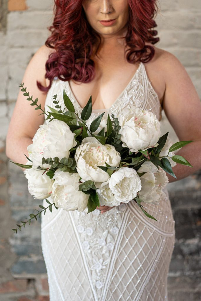 A bride with a large white peony bridal bouquet from the Lhasa Collection.