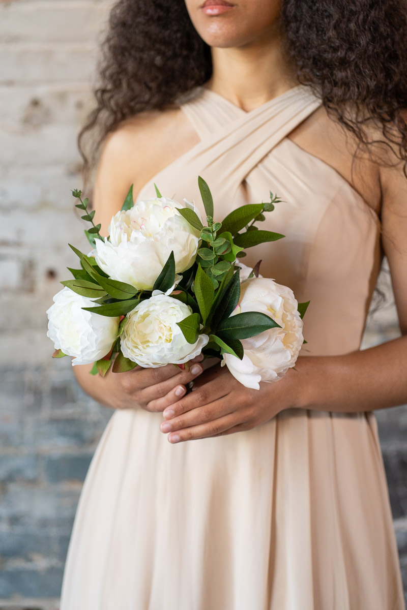 A bridesmaid in a tan dress with a white peony bouquet from the Lhasa Collection