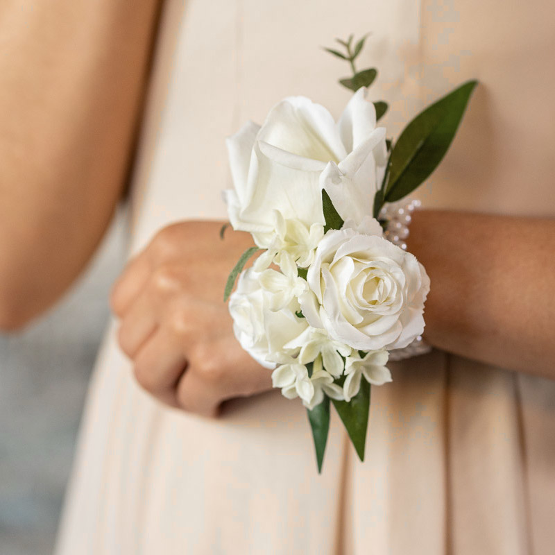A white rose corsage on a bridesmaid in a tan dress.