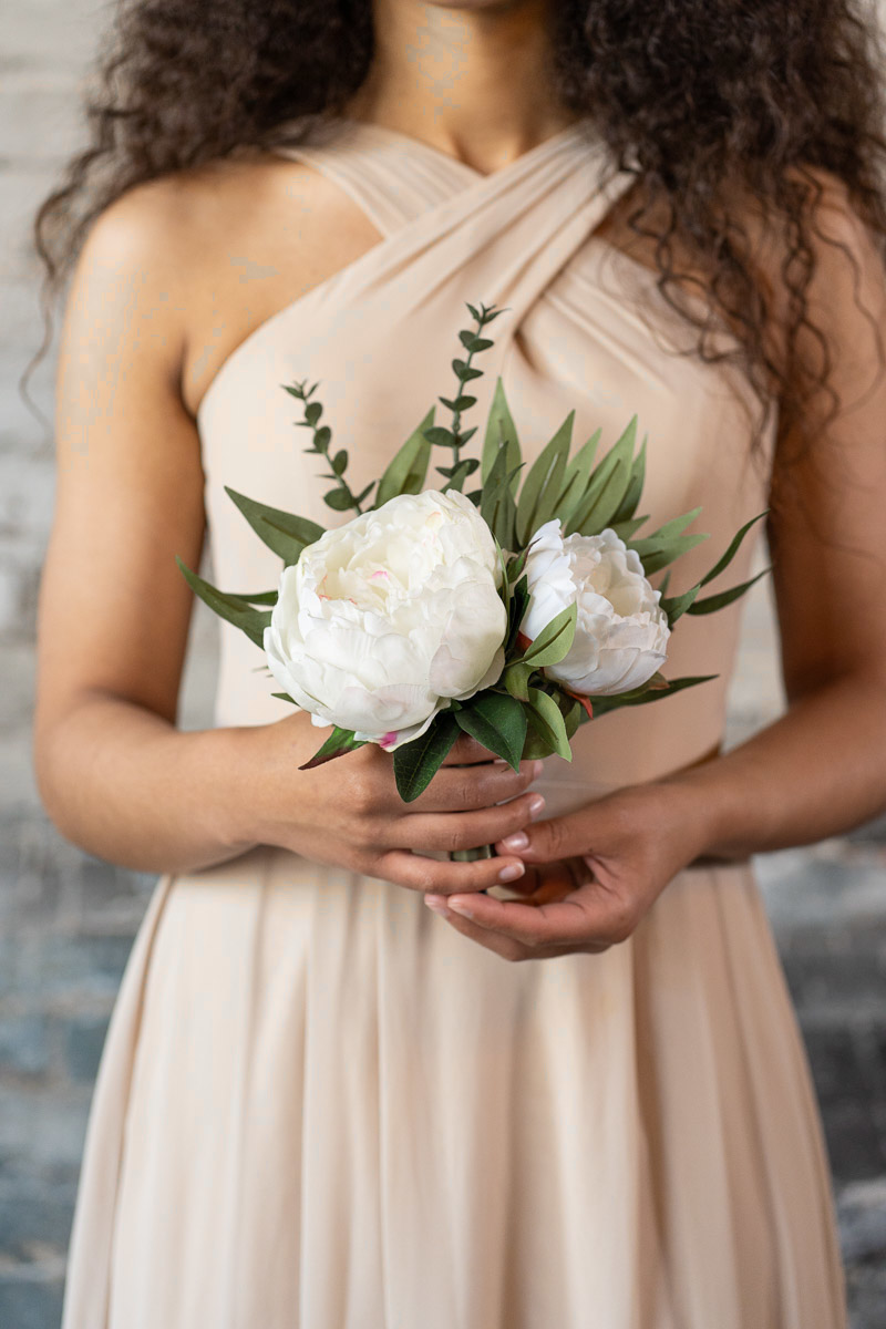 A bridesmaid in a tan dress with a mini white peony bouquet from the Lhasa Collection