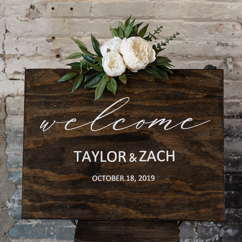 A wood wedding sign with a white peony floral swag.