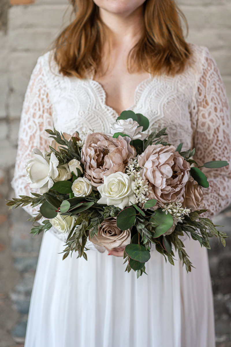 A bride with a mauve peony and white rose bridal bouquet from the Montreal Collection.