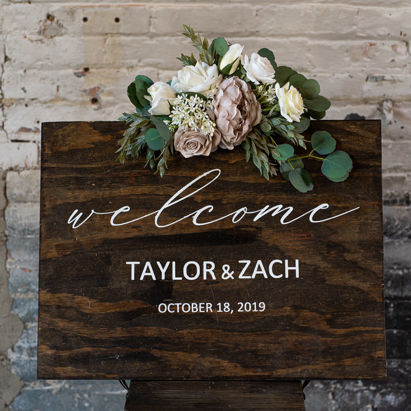 A wood sign with a white rose and mauve peony sign swag.