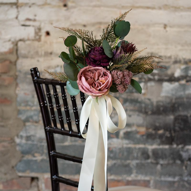 A pink and purple aisle marker with juniper and silver dollar eucalyptus from the Odessa collection.