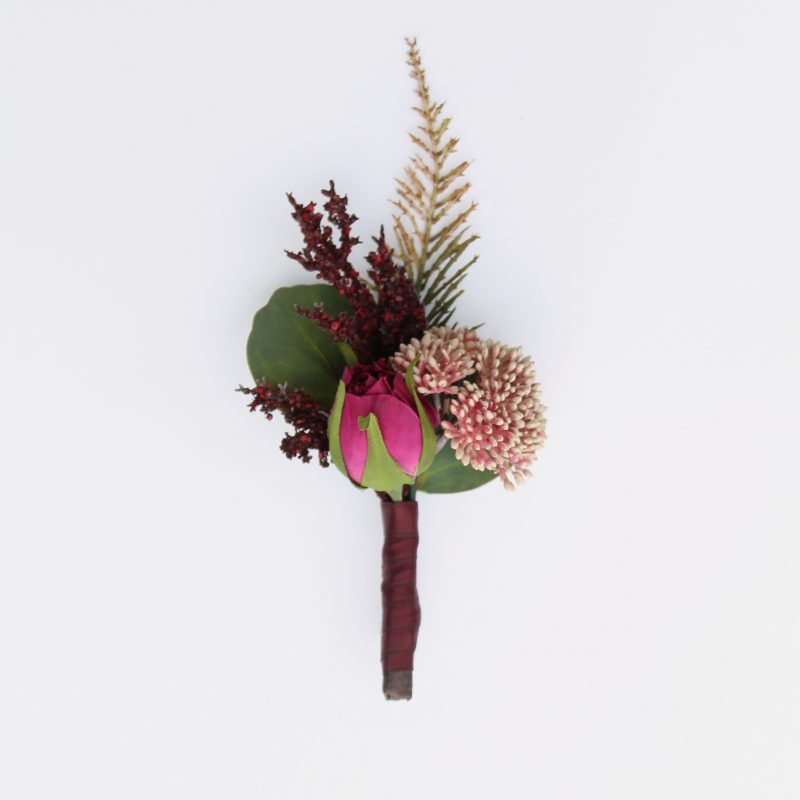A purple and pink rosebud boutonniere from the Odessa Collection.