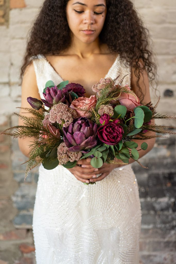 A pink and purple bridal bouquet with juniper and silver dollar eucalyptus from the Odessa collection.