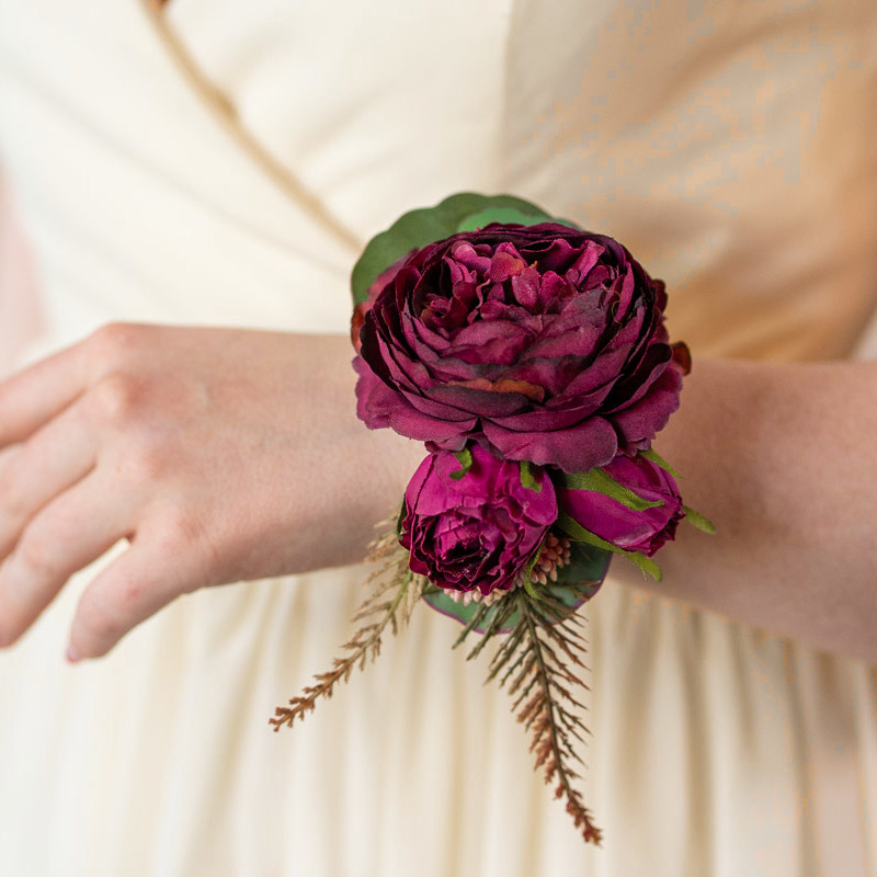 A purple ranunculus corsage with a tan bridesmaid dress.