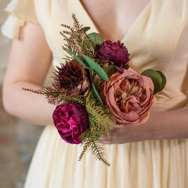 A pink and purple bridesmaid bouquet with juniper and silver dollar eucalyptus from the Odessa collection.