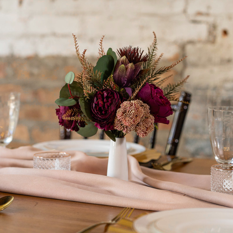 A pink and purple centerpiece with juniper and silver dollar eucalyptus from the Odessa collection.