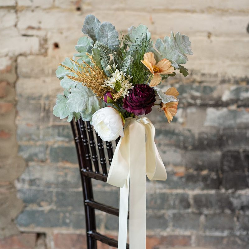 A wildflower aisle marker tied to a Chiavari chair with ivory ribbon.