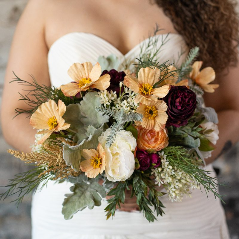A wildflower bridal bouquet with magenta roses and peach anemones from the Oslo Collection.