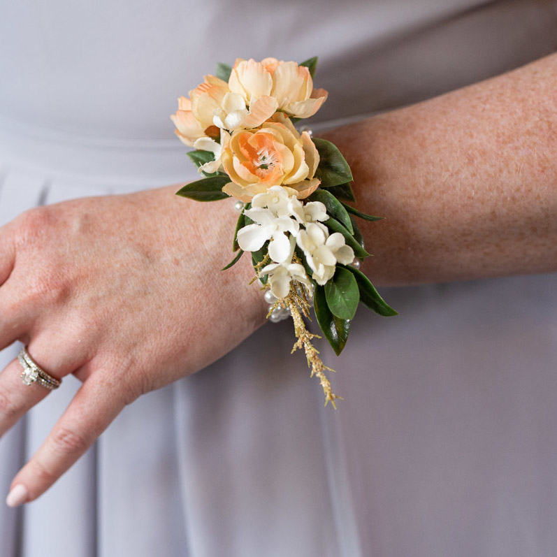 A wrist corsage from the Oslo Collection with small peach rose buds.