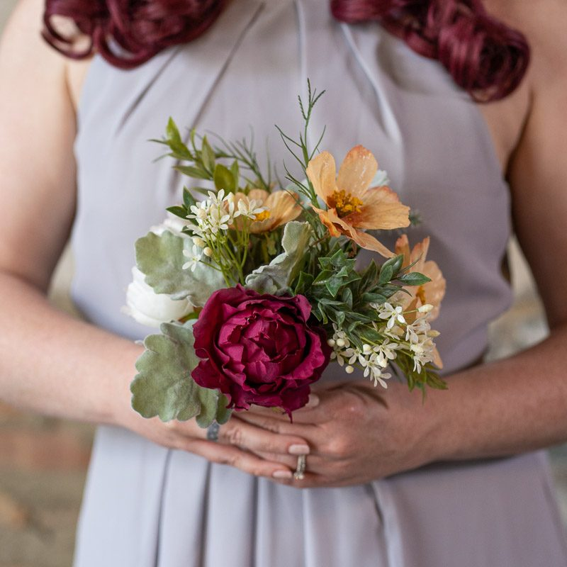 A wildflower bridesmaid bouquet with magenta roses and peach anemones from the Oslo Collection.