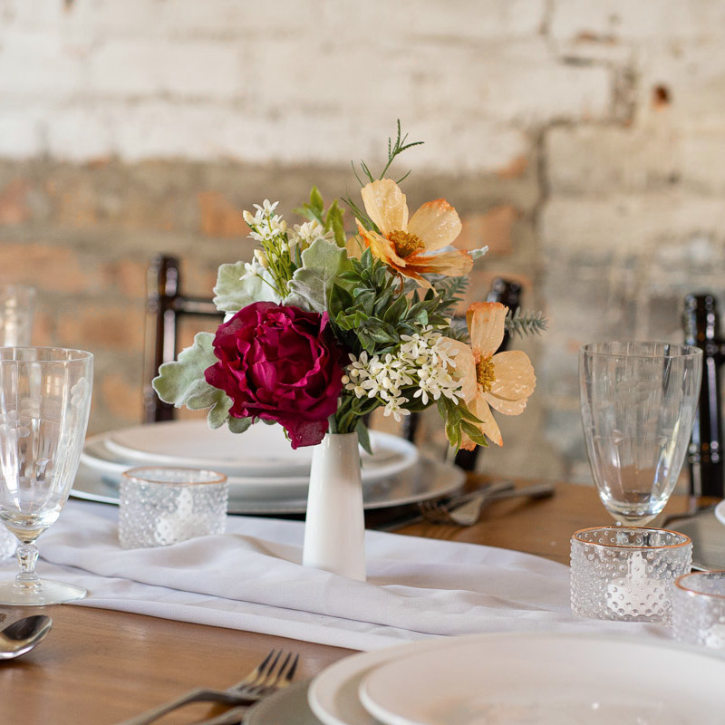 A wildflower centerpiece with magenta roses and peach anemones.