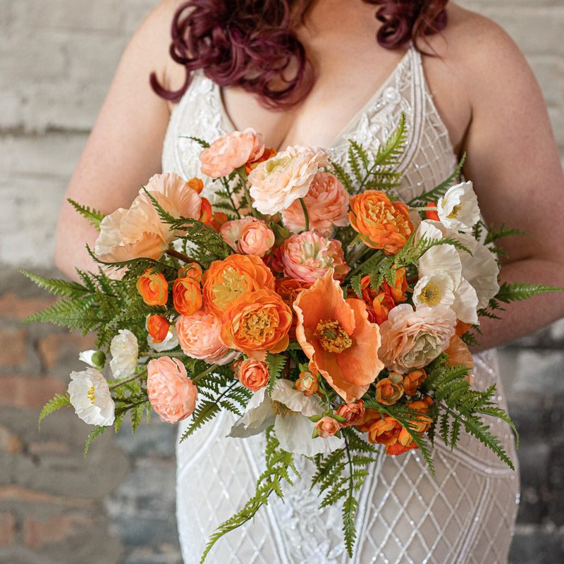 A bride with an orange bouquet with poppies and ranunculus.