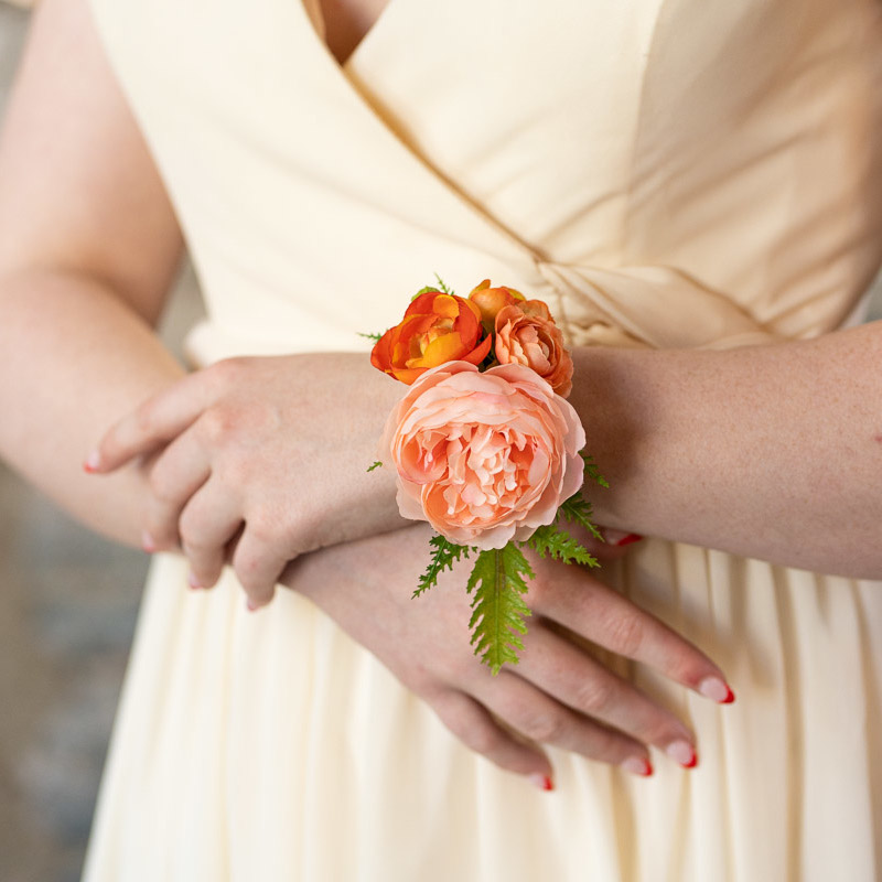 An orange and pink ranunculus corsage from the Santiago Collection.