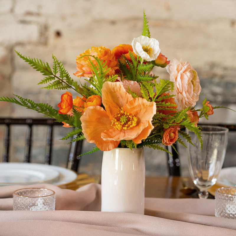 A centerpiece with orange ranunculus and pink camellias from the Santiago Collection.