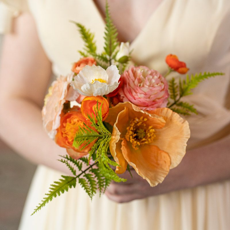A bridesmaid with an orange bouquet with poppies and ranunculus.